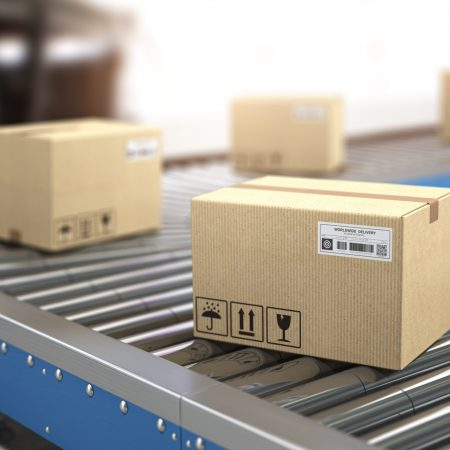 Сardboard boxes on conveyor in warehouse. Delivery, storage and distribution service concept.