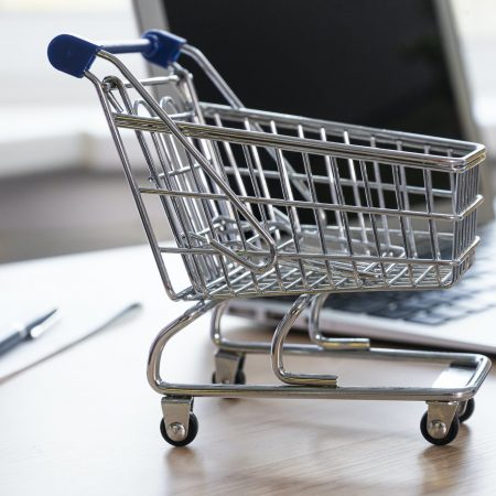Mini empty shop cart trolley over a laptop computer on wood table background